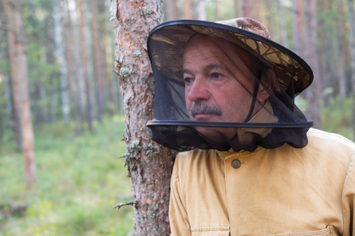 Man wearing a midge net protecting his head